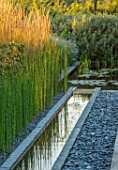 PRIVATE GARDEN, SURREY: DESIGNER ANTHONY PAUL: GRANITE RILL, POND, POOL, WATER, PEBBLES, FEATURE, REEDS, EQUISETUM, HYEMALE, HORSETAIL, GREEN, FOLIAGE, GRASS, PERENNIALS, DECKING