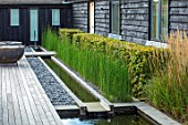 PRIVATE GARDEN, SURREY: DESIGNER ANTHONY PAUL: DECKED GARDEN, DECKING, FORMAL, SMALL, ENGLISH, COUNTRY, GRANITE RILL, WATER, POND, POOL, SPOUT, PEBBLES, HEDGE, EQUISETUM HYEMALE