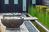 PRIVATE GARDEN, SURREY: DESIGNER ANTHONY PAUL: DECKED GARDEN, CONTAINERS, WATERLILIES. DECKING, ROUND, CIRCULAR, FORMAL, SMALL, ENGLISH, COUNTRY, RILL, EQUISETUM HYEMALE, HORSETAIL