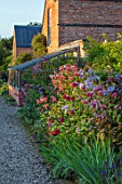 MORTON HALL GARDENS, WORCESTERSHIRE: KITCHEN GARDEN. LILIUM SPECIOSUM BLACK BEAUTY AND CLEMATIS VITICELLA EMILIA PLATER. BULB, CLIMBER, CLIMBERS, WALL, WALLED, BORDER, BED