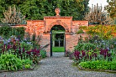 MORTON HALL GARDENS, WORCESTERSHIRE: KITCHEN GARDEN IN LATE SUMMER. BEDS WITH AMARANTHUS, GATE, WALL, WALLED, COUNTRY, HOUSE, CLASSIC, VEGETABLE, ARCH