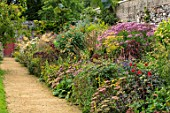 PARHAM, SUSSEX: PATH, RED DOOR. HOT BORDER - TITHONIA TORCH, DAHLIA BISHOP OF LLANDAFF, SEDUM MATRONA, HELIANTHUS LEMON QUEEN, AGASTACHE BLACK ADDER, BORDERS, WALLED, GARDEN