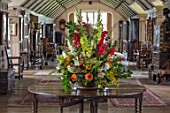 PARHAM, SUSSEX: THE LONG GALLERY - CONTAINER FLOWER DISPLAY WITH GLADIOLUS. DAHLIAS, ZINNIAS, FOLAIGE OF BEECH, OAK, COTINUS. DISPLAY, CUTTING, ARRANGEMENT
