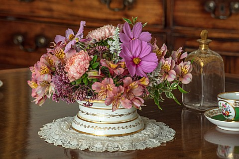 PARHAM_SUSSEX_GREEN_ROOM__WHITE_AND_GOLD_CONTAINER_WITH_PINK_ALSTROEMERIA_COSMOS_RHAMNUS_WHITE_SALVI