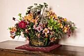 PARHAM, SUSSEX: HALL - PINK WALL, TABLE,  CONTAINER WITH SEDUM AUTUMN JOY, ALSTROEMERIA, GOLDEN PRIVET, RED DAHLIAS