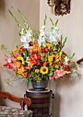 PARHAM, SUSSEX: ENTRANCE HALL - CONTAINER WITH SUNFLOWERS, RED ALSTROEMERIA, GLADIOLUS AND BRONZE FENNEL