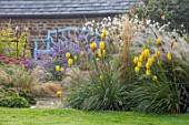 PETTIFERS, OXFORDSHIRE: BLUE WOODEN BENCH, SEAT, BORDER WITH KNIPHOFIA SUNNINGDALE YELLOW, JAPANESE ANEMONES, ASTERS. PERENNIALS, LATE SUMMER, FALL, AUTUMN