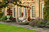 BOURTON HOUSE GARDEN, GLOUCESTERSHIRE: LAWN, HOUSE, STONE , AUTUMN, FALL, SEPTEMBER, ENGLISH, LATE, SUMMER, TRAINED PYRACANTHA ON WALL, URNS, CONTAINERS, PARROTIA PERSICA