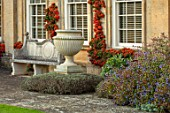 BOURTON HOUSE GARDEN, GLOUCESTERSHIRE: LAWN, HOUSE, STONE , AUTUMN, FALL, SEPTEMBER, ENGLISH, LATE, SUMMER, TRAINED PYRACANTHA ON WALL, URNS, CONTAINERS, CERATOSTIGMA