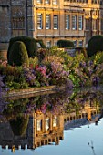 FORDE ABBEY, SOMERSET: VIEW OF THE LONG POND IN OCTOBER, DAWN, SUNRISE, WATER, FORMAL, POND, POOL, CLIPPED, YEW, TOPIARY, AUTUMN, ENGLISH, COUNTRY, GARDEN, REFLECTIONS, REFLECTED