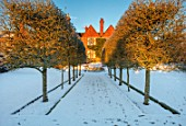 FELLEY PRIORY, NOTTINGHAMSHIRE: WINTER - SNOW. VIEW TO PRIORY ALONG AVENUE OF HAWTHORN - CRATAEGUS TANACETIFOLIUM. DECEMBER. ENGLISH, COUNTRY, GARDEN, SUNRISE, DAWN, FROZEN