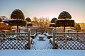 FELLEY PRIORY, NOTTINGHAMSHIRE: WINTER - THE WHITE GARDEN, SNOW, FROST, CLIPPED TOPIARY SHAPES OF PHILLYREA LATIFOLIA, TRELLIS FENCING, DAWN, SUNRISE, DECEMBER, FORMAL, ENGLISH