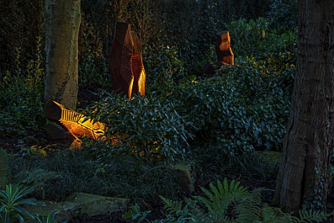 MORTON_HALL_GARDENS_WORCESTERSHIRE_WOOD_SCULPTURE_FROM_FELLED_WELLINGTONIA_IN_THE_ROCKERY_EVENING_LI