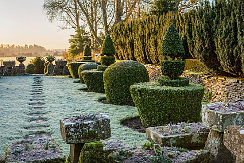RODMARTON_MANOR_GLOUCESTERSHIRE_WINTER_FEBRUARY__FROST_PATH_TROUGHERY_STONE_URNS_CONTAINERS_DAWN_LIG