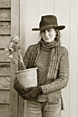 HERTFORDSHIRE HELLEBORES, LORNA JONES: BLACK AND WHITE IMAGE OF LORNA JONES HOLDING A TERRACOTTA CONTAINER OF HELLEBORES