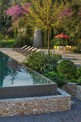 SKOPOS_DESIGN_CORFU_RAISED_BLACK_INFINITY_POOL_WITH_REFLECTIONS_PATIO_AREA_PAVED_SEATING_DINING_CHAI