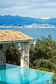 SKOPOS DESIGN, CORFU: SWIMMING POOL, LOGGIA AND VIEW OF ALBANIAN MOUNTAINS. WATER, MEDITERRANEAN, GARDENS