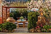 ASCOT SPRING GARDEN SHOW: GARDEN DESIGNED BY KATE GOULD: TABLE, CHAIRS, TERRACOTTA CONTAINER, CORTEN STEEL PERGOLA, SCREENS, SCREENING, DINING, FORMAL, URBAN, SMALL, CHERRY, PRUNUS