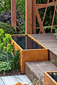 ASCOT SPRING GARDEN SHOW: GARDEN DESIGNED BY KATE GOULD: CORTEN STEEL WATER TROUGH, FEATURE, POND, POOL. BAMBOO DECKING, DECK