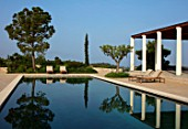 PORTO HELI, GREECE, DESIGNER THOMAS DOXIADIS: VILLA GARDEN. SWIMMING POOL, PINE TREE, OLIVE TREE, SUN LOUNGERS, MEDITERRANEAN, WILD, DRY, GREEK, DAWN, REFLECTIONS, REFLECTED