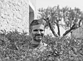 PORTO HELI, GREECE, DESIGNER THOMAS DOXIADIS: BLACK AND WHTE PHOTOGRAPH - THOMAS IN A HEDGE OF PISTACIA LENTISCUS