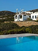 ANTIPAROS, GREECE, DESIGNER THOMAS DOXIADIS: SWIMMING POOL, WHITE PAINTED VILLA WITH WHITE METAL OLIVE TREE SCULPTURE, GREEK, LANDSCAPE