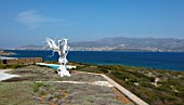 ANTIPAROS, GREECE, DESIGNER THOMAS DOXIADIS: VILLA GARDEN WITH WHITE METAL OLIVE TREE SCULPTURE LOOKING OUT TO SEA
