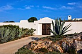 ANTIPAROS, GREECE, DESIGNER THOMAS DOXIADIS: VILLA GARDEN WITH AGAVE CACTUS, ROCK AND WHITE WALL, AGAVE AMERICANA