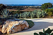 ANTIPAROS, GREECE, DESIGNER THOMAS DOXIADIS: VILLA GARDEN WITH DRIVE, AGAVE CACTUS, ROCK AND WHITE WALL, AGAVE AMERICANA