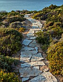 ANTIPAROS, GREECE, DESIGNER THOMAS DOXIADIS:PATH DOWN TO SEA SURROUNDED BY SHRUBS. DRY, GARDEN, SPRING, MEDITERRANEAN, LANDSCAPE