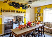 THE OLD PARSONAGE, LITTLE BREDY, DORSET: THE KITCHEN WITH DINING TABLE AND CHAIRS, SOFA, RANGE COOKER. TULIPS PICKED FROM THE GARDEN IN VASES.YELLOW INTERIOR, HOME,COUNTRY STYLE.