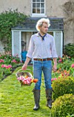 THE OLD PARSONAGE, DORSET: OWNER CHARLIE MCCORMICK IN HIS FRONT GARDEN WITH TRUG OF PICKED TULIPS