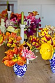 THE OLD PARSONAGE, DORSET: KITCHEN TABLE WITH TULIPS PICKED FROM THE GARDEN IN VASES. ORANGE, STRIPED, YELLOW, COLOURFUL, FLOWER, INTERIOR, HOME, ORNAMENTAL,DECORATIVE.CANDLES.