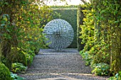 MITTON MANOR, STAFFORDSHIRE: PATH, TOPIARY, AVENUE, FORMAL, COUNTRY, BOX, TOPIARY, HEDGES, HEDGING, EVERGREEN, SPRING, STEEL, ALLIUM, SPHERE, SCULPTURE BY RUTH MOILLIET