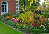 MORTON HALL, WORCESTERSHIRE: BORDER WITH PINK AND TULIPS BESIDE LAWN - TULIPA MARIETTE, SPRING GREEN, LASTING LOVE, RECREADO, BULBS, LAWN, BORDERS, FLOWERS, FLOWERING