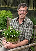 AVONDALE NURSERIES, COVENTRY: NURSERY OWNER BRIAN ELLIS HOLDING BASKET OF LILY-OF-THE-VALLEY - CONVALLARIA MAJALIS, MAN, SITTING, GARDENER