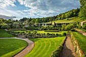 CHILWORTH MANOR, SURREY: WALLED GARDEN, LAWN, WALLS, SLOPE, SLOPING, LANDSCAPE, BORROWEDWHITE WISTERIA, SPRING