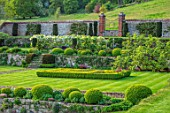 CHILWORTH MANOR, SURREY: WALLED GARDEN, LAWN, WALLS, SLOPE, SLOPING, LANDSCAPE, BORROWEDWHITE WISTERIA, SPRING, PARTERRE, GATE, BOX BALLS