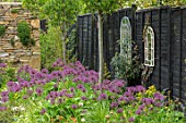 THE MOONGATE GARDEN, SUSSEX: PATH, BORDERS IN SPRING OF ALLIUM FIRMAMENT WITH PURBECK STONE WALL, BLACK PAINTED FENCE, MIRRORS, BOUNDARY, BOUNDARIES, BULBS