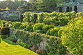 CHILWORTH MANOR, SUSSEX: THE WALLED GARDEN. STEPS, WALLS, CLIPPED TOPIARY BOX, BUXUS, GATE, BORROWED LANDSCAPE, WHITE WISTERIA