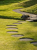 CHILWORTH MANOR, SUSSEX: CIRCULAR STEPPING STONES ACROSS LAWN IN SPRING.