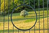 CHILWORTH MANOR, SUSSEX: METAL GATE IN THE WALLED GARDEN WITH VIEW TO TREE AND LANDSCAPE BEYOND. SPRING