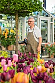 CLAUS DALBY GARDEN, DENMARK: CLAUS DALBY PHOTOGRAPHING TERRACOTTA CONTAINERS OF TULIPS ON TERRACE, PATIO
