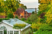 CLAUS DALBY GARDEN, DENMARK: VIEW TO SEA WITH TREES, GREENHOUSE, GARDEN BUILDING, CONSERVATORY