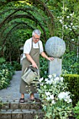CLAUS DALBY GARDEN, DENMARK: CLAUS DALBY WATERING CONTAINERS IN THE SUNKEN GARDEN, SPRING. STEPS, TERRACOTTA CONTAINERS WITH TULIPS - TULIPA WGITE TRIUMPHATOR, PATIO, TERRACE