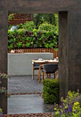 CHELSEA FLOWER SHOW 2018: URBAN FLOW GARDEN, DESIGNER TONY WOODS. VIEW THROUGH PORCELAIN, STEEL EFFECT ARCH TO TABLE, PATIO, LIVING WALL, KITCHEN, DINING AREA, ENTERTAINING