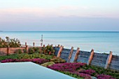 SEASIDE GARDEN DESIGNED BY ANTHONY PAUL: INFINITY SWIMMING POOL, OAK FENCES, THRIFT, ARMERIA MARITIMA, PINK, FLOWERS, SPRING, COASTAL, GARDENS, ERIGERON SEABREEZE
