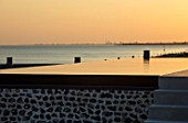 SEASIDE GARDEN DESIGNED BY ANTHONY PAUL: INFINITY SWIMMING POOL IN EVENING WITH VIEW TO SEA AND PORTSMOUTH