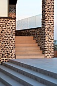 SEASIDE GARDEN DESIGNED BY ANTHONY PAUL: STEPS BESIDE PATIO AND MODERN HOUSE