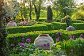 MITTON MANOR, STAFFORDSHIRE:FORMAL PARTERRE. STONE BALL, BOX EDGED BEDS. HEDGES, HEDGING, SPRING, TERRACOTTA CONTAINERS, ALLIUM PURPLE SENSATION,NEIL WILKIN GLASS SCULPTURES